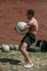 Athlete with physical disability carrying atlas stone outdoors
