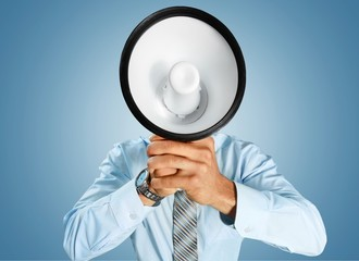 Young businessman talking on the megaphone on white background