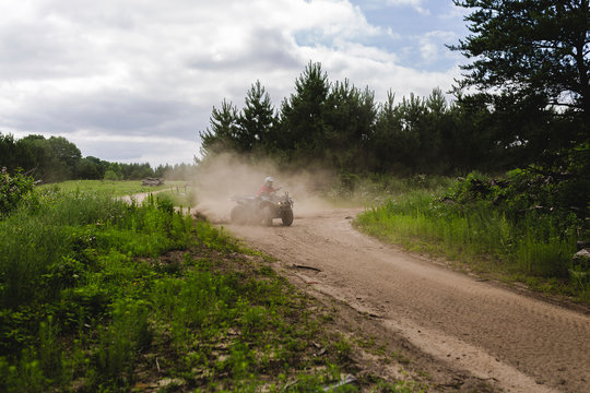 Teenage boy riding quad bike on dirt road