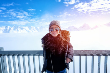 Young Woman Tourist at the Schilthorn in Switzerland with a magnificent panoramic view of the Swiss Skyline.
