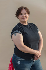 Portrait of confident overweight woman standing against colored background