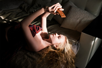 High angle view of woman in off shoulder dress taking selfie with smart phone while lying on bed at home