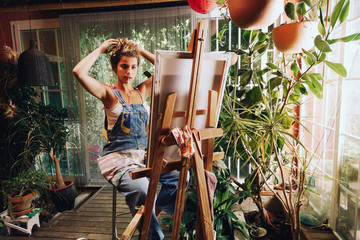 Confident female artist tying hair while painting in studio