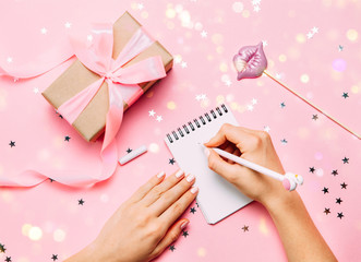 Beautiful female hands with trendy manicure writing in notebook. gift box holigay accessories aronhd. Christmas greeting concept. Blogger working process. Blogging concept. Top view, flat lay.