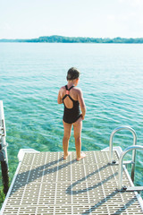 Rear view of wet girl in swimwear standing on pier over lake against sky