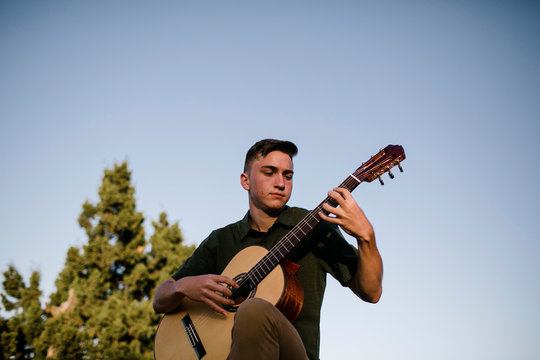 Young man playing guitar while sitting on rock during sunset