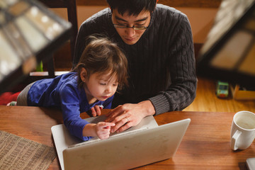 High angle view of father with cute daughter using laptop computer on wooden table at home