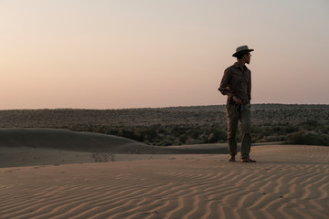 Man looking away while standing at Thar Desert against clear sky during sunset