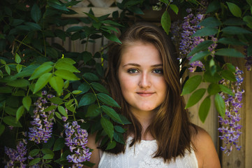 Close-up portrait of smiling teenage girl standing amidst plants at park