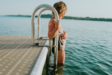 Side view of girl wearing swimwear while standing on ladder in lake against sky