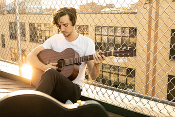 Man playing guitar while sitting by chainlink fence against building during sunset