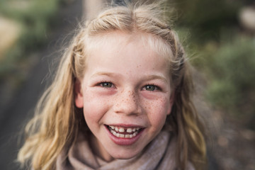 Close-up portrait of happy girl with blond hair standing in forest