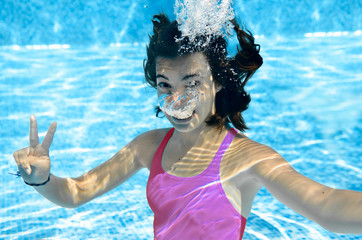 Girl swims in swimming pool underwater, happy active teenager dives and has fun under water, kid fitness and sport on family vacation on resort