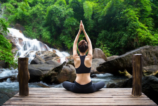 Healthy woman lifestyle balanced practicing meditate and zen energy yoga on the bridge in morning the waterfall in nature forest. Healthy life Concept.