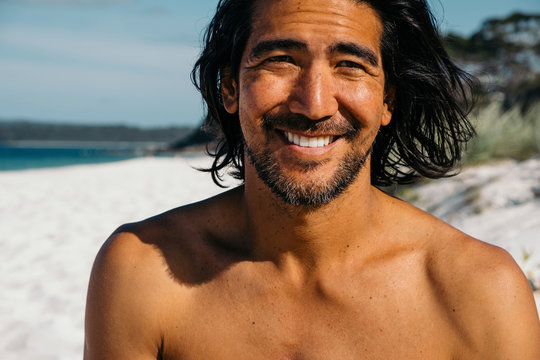 Close-up of happy shirtless man looking away while sitting at Hyams Beach during against sky sunny day
