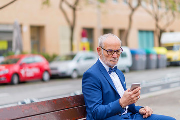Confident senior man in suit using smart phone while sitting on bench against building