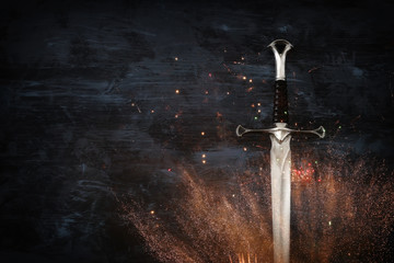 low key image of silver sword with fire sparks. fantasy medieval period. Wall mural