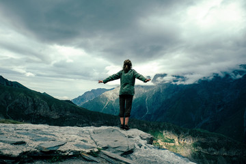 Rear view of woman with arms outstretched standing on mountain against cloudy sky