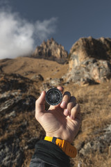 A male Hiker is looking for a direction with a magnetic compass in the mountains in the fall. Point of view shot. Man's hand with a watch bracelet holds a compass