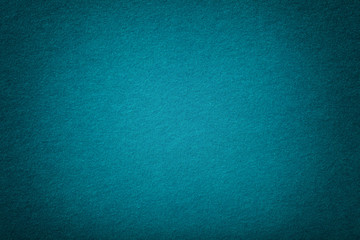 Dark turquoise matt suede fabric closeup. Velvet texture of felt.