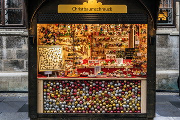 Vienna, Austria - December 21, 2017. Winter seasonal stand selling Christmas glass ornaments and souvenirs at traditional Xmas market. Illuminated fair kiosk with decor near St. Stephen's Cathedral.