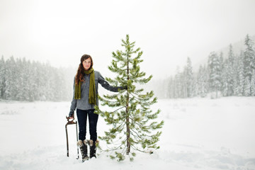 Portrait of woman holding pine tree while standing on snow covered field against sky in forest