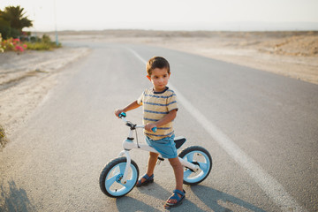 Boy with bicycle standing on road