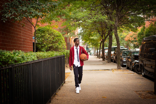 Student with basketball listening to music while walking on sidewalk