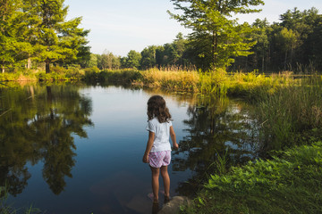 Rear view of girl standing at lakeshore in forest