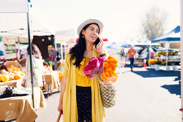 Mature woman answering smart phone while shopping at farmer's market during sunny day