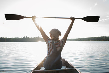 Rear view of woman with arms raised holding oar while sitting in boat on lake at Algonquin Provincial Park