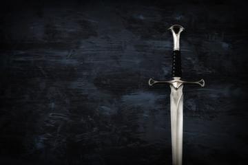 low key image of silver sword. fantasy medieval period.
