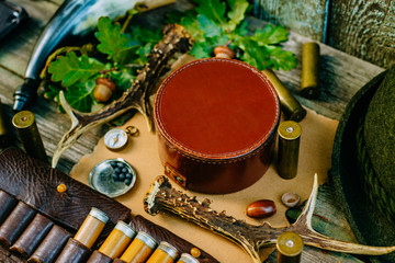Closeup round leather hunt box for information among hunting or tourist equipment.