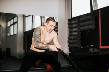 Shirtless young man screaming while using battle ropes in gym