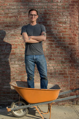 Portrait of businessman with arms crossed standing in wheelbarrow on sidewalk against brick wall