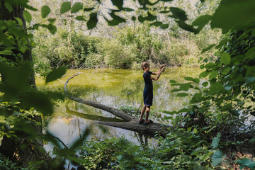 Full length of boy with fishing rod standing on fallen tree in lake at forest
