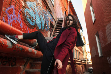 Low angle portrait of confident woman wearing red coat while climbing on building in city