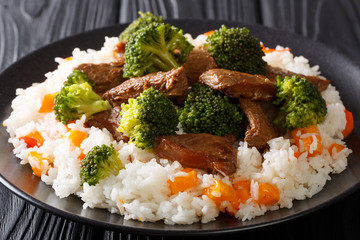 Delicious healthy beef with broccoli garnished with rice and persimmon closeup on a plate. horizontal