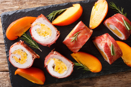 Delicious pork tenderloin stuffed with persimmon and cheese wrapped in prosciutto close-up. Horizontal top view