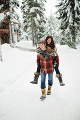 Boyfriend piggybacking girlfriend while walking on snow covered field in forest