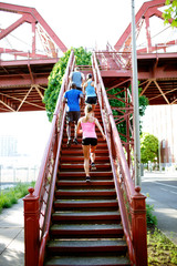 Low angle view of friends running on steps in city