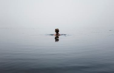 Rear view of woman swimming in river during foggy weather