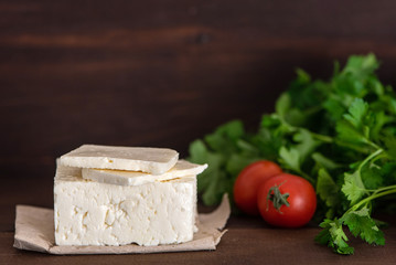 Large piece of feta cheese on dark wooden table. Selective focus