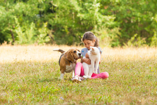 Portrait of girl sitting on a grassy ground together with her pets