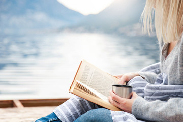 Girl is reading book on wooden pier by winter sea, mountains, beach. Cozy picnic with hot steamy...