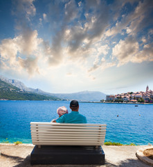 Young couple is sitting on the bench in front of sea