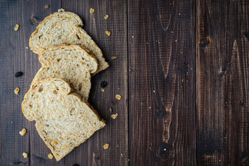 Whole wheat, whole grains bread on dark wooden board, close up, top view