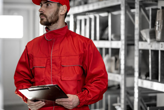 Warehouse worker in red uniform checking goods standing with clipboard in the storage with metal shelves