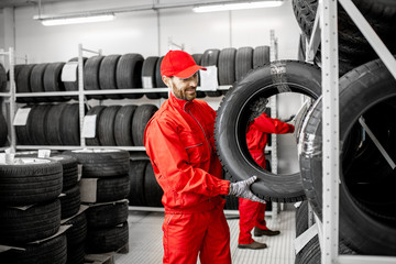 Two men in red uniform working in the warehouse with new car tires Wall mural