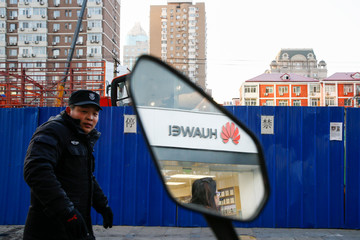 A security guard walks past a Huawei phone retailer as the company logo is reflected in a mirror in Beijing